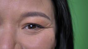 Tiro da metade-cara do close up da cara fêmea asiática atrativa nova com os olhos que olham em linha reta na câmera com o sorriso vídeos de arquivo
