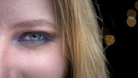 Tiro da metade-cara do close up da cara fêmea bonita nova com os olhos que olham a composição bonito da câmera com o fundo is video estoque