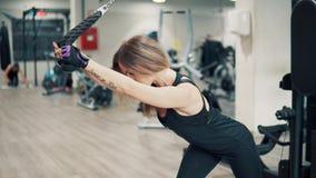 Tiro da mulher nova do ajuste que faz o exercício do tríceps usando a máquina de formação no gym video estoque