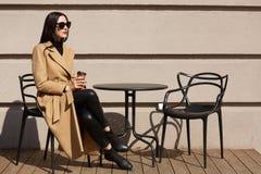 Tiro da mulher que veste o revestimento elegante que come o café da manhã no café exterior da rua acolhedor e que bebe o café da  imagens de stock royalty free