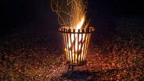 Tiro da noite de um fogo ardente em uma cesta do metal com as folhas na terra imagens de stock