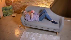 Tiro da opinião superior do close up da fêmea loura caucasiano adulta que usa o telefone ao encontrar-se no sofá e alegremente ao video estoque