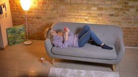 Tiro da opinião superior do close up da fêmea loura caucasiano adulta que usa o telefone ao encontrar-se no sofá e ao ser relaxad filme