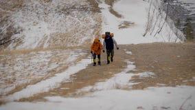 Tiro da parte superior do monte de dois caminhantes que trekking no inverno Eles que vão com cuidado subidas que cobriram na neve video estoque