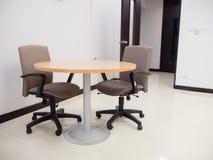 Tiro da sala de reunião vazia com mesa redonda e confortável largos Imagens de Stock Royalty Free