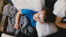 Tiro da vista superior de pouco menino caucasiano das pessoas de 4-6 anos que dorme em um descanso branco confortável durante o v vídeos de arquivo