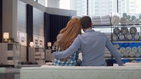 Tiro da vista traseira de um par que abraça, sentando-se em uma cama nova na loja de móveis filme