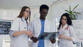Tiro da zorra de três multi doutores nacionais que discutem o raio X dos pulmões do paciente doente video estoque