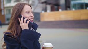 Tiro da zorra do smartphone de fala da menina atrativa da raça misturada e de caminhadas bebendo do café na rua da cidade Mulher  video estoque