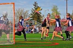 Tiro das meninas da lacrosse sob o bloco Fotografia de Stock Royalty Free