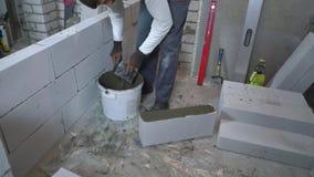Tiro de ângulo alto do construtor que põe o almofariz sobre o lado do bloco de cimento ventilado filme