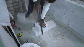 Tiro de ângulo alto do construtor que vê o bloco de cimento ventilado após ter medido o video estoque