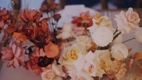 Tiro de ângulo alto do ramalhete bonito do casamento na mesa de jantar decirated filme