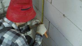 Tiro de alto ángulo del carril de fijación del metal del trabajador con la abrazadera en la pared del bloque de cemento metrajes