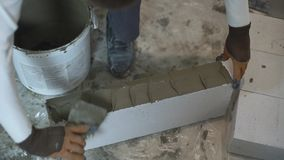 Tiro de alto ángulo de las manos del constructor que ponen el mortero en lados del bloque con la espátula metrajes