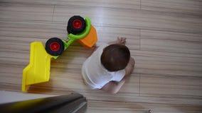 Tiro de alto ángulo, siete meses lindos del bebé que juega con los juguetes educativos en el piso almacen de video
