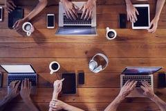 Tiro de arriba de adultos jovenes usando tecnología en una tabla Imagen de archivo libre de regalías