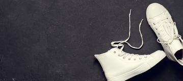 Tiro de arriba de las zapatillas de deporte blancas en fondo negro Imagen de archivo