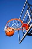 Tiro de baloncesto que cae a través de la red, cielo azul Imagen de archivo libre de regalías