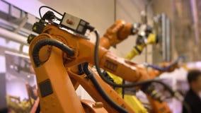 Tiro de diversos lentamente brazos robóticos automáticos móviles en proceso en fondo de la exposición almacen de metraje de vídeo