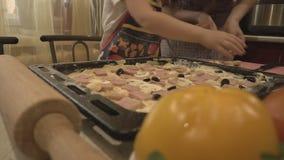 Tiro de dos amas de casa en aceitunas crudas de la pizza metrajes