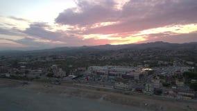 Tiro de elevación aéreo de una puesta del sol en una ciudad en la playa metrajes