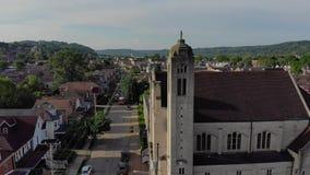 Tiro de establecimiento aéreo de baja lento de la pequeña ciudad y de la iglesia metrajes