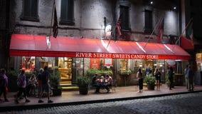 Tiro de establecimiento exterior de la noche de la tienda de chucherías de los dulces de la calle del río metrajes
