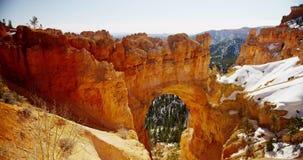Tiro de filtrado vertical del arco de piedra rojo y del valle nevoso en 4K almacen de video