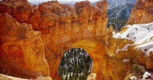 Tiro de filtrado vertical del arco de piedra rojo y del valle nevoso en 4K metrajes