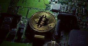 Tiro de giro de um bitcoin de Casascius em uma placa de circuito verde video estoque