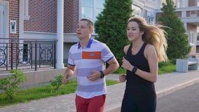 Tiro de la cámara lenta de un hombre adulto y de una mujer atractiva en un traje de los deportes que corre a lo largo de la calle almacen de metraje de vídeo
