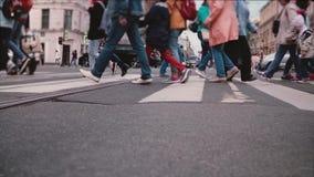 Tiro de la cámara lenta del ángulo bajo de las piernas y de los pies de la gente que cruzan una calle ocupada de la ciudad, bicic metrajes