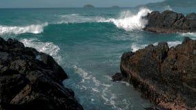 Tiro de la cámara lenta de las ondas grandes del mar que se estrellan contra las rocas Ondas que se estrellan y que golpean en la almacen de video