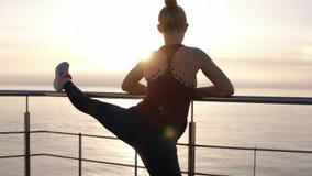 Tiro de la cámara lenta de la mujer joven deportiva concentrada que estira las piernas en el embarcadero de madera con la cerca d almacen de metraje de vídeo