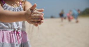 Tiro de la cámara lenta de una niña en la playa, sosteniendo la arena a disposición y dejándola caer abajo arena otra vez, cámara almacen de video