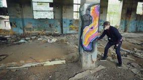 Tiro de la cacerola del artista enmascarado de la pintada que dibuja imágenes abstractas en pilar en el edificio vacío grande usa almacen de metraje de vídeo