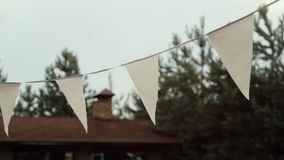 Tiro de la cacerola de izquierda a derecha de las banderas blancas que cuelgan en espacio abierto cerca de la cabaña metrajes