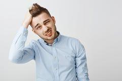Tiro de la cintura-para arriba del hombre de negocios joven hermoso perplejo y preocupado en pelo principal inclinable del frotam foto de archivo libre de regalías