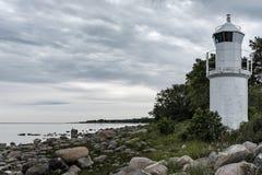 Tiro de la costa rocosa hermosa del mar con una torre blanca del faro en el lado imagen de archivo libre de regalías