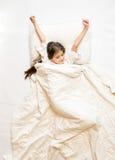 tiro de la muchacha linda que está despierta y que estira en cama Foto de archivo libre de regalías