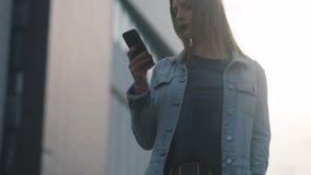 Tiro de la muchacha modelo hermosa joven del estudiante de la moda con los labios rojo oscuro en corte azul del dril de algodón y almacen de metraje de vídeo