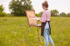 Tiro de la muchacha rubia con la imagen de la pintura del bollo en sketchbook en naturaleza, la mujer joven implicada en creativi foto de archivo