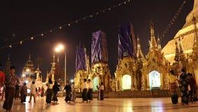 Tiro de la noche del lapso de tiempo de la gente que camina en la pagoda de Shwedagon, tambi?n conocido como la pagoda de oro Es  almacen de video