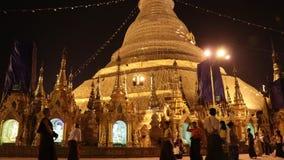 Tiro de la noche del lapso de tiempo de la gente que camina en la pagoda de Shwedagon, tambi?n conocido como la pagoda de oro metrajes