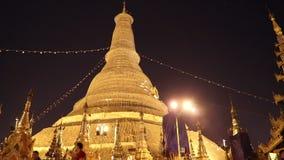 Tiro de la noche de la gente que camina en la pagoda de Shwedagon, tambi?n conocido como la pagoda de oro Es un stupa dorado en e almacen de metraje de vídeo
