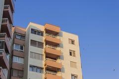 Tiro de la perspectiva del edificio moderno construido reforzado de color naranja urbano alto con el cielo azul en Esmirna en Tur fotos de archivo libres de regalías