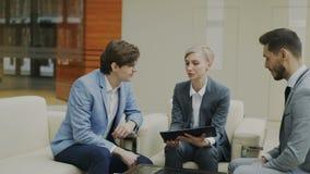 Tiro de la toma panorámica de la empresaria con la tableta digital duscussing con los colegas masculinos del negocio que se sient