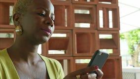 Tiro de mano de la mujer de negocios afroamericana negra atractiva y feliz que usa el mensaje que mecanografía que manda un SMS d