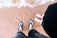 Tiro de mirada hacia abajo de los pares que se colocan en una playa con las ondas c Imagen de archivo